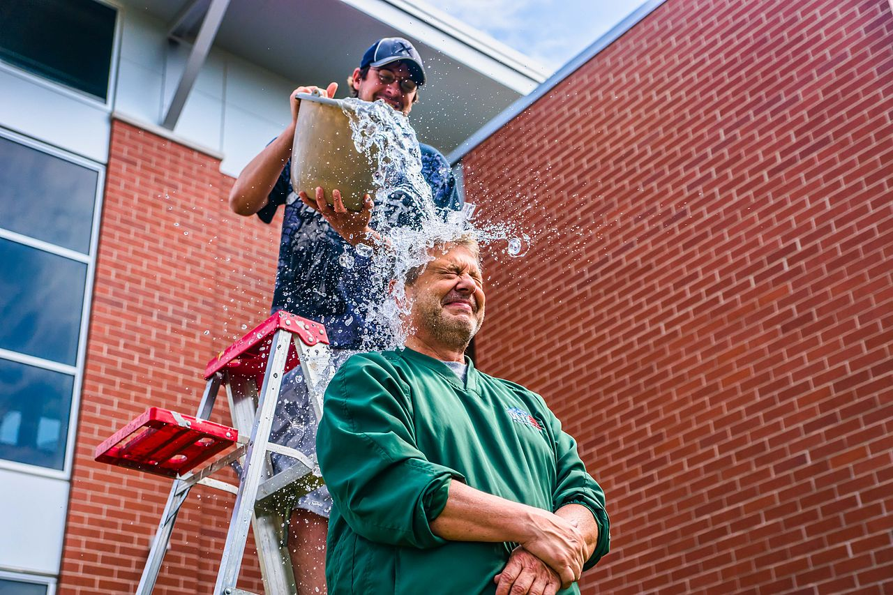 Image of a person in green being dumped with a bucket of ice water